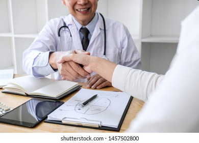 Professional Male doctor in white coat shaking hand with female patient after successful recommend treatment methods, Medicine and health care concept.