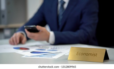 Professional male economist scrolling on smartphone, working on market research