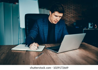 Professional male finance manager checking accountings in app on laptop computer planning budget in notebook,skilled economist reading information.