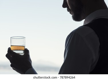Professional male holding glass of amber colored alcohol