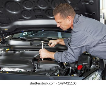 a professional male mechanical employee of the car service workshop make some repairs with the tool at the open bonnet motor engine and unscrew smething in a grey work wear in the garage