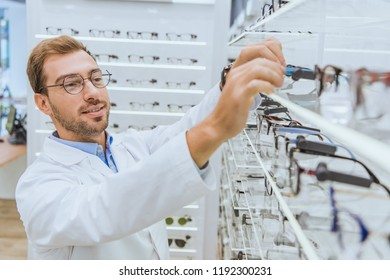 professional male oculist in white coat taking glasses from shelves in optica