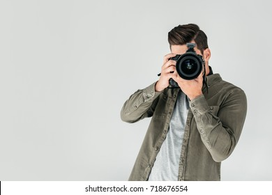 professional male photographer with digital photo camera in photo studio, isolated on grey