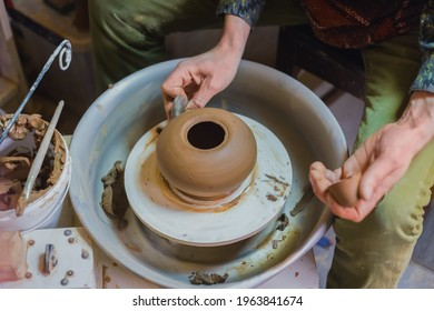 Professional male potter shaping pot with special tool in pottery workshop, studio. Crafting, artwork and handmade concept