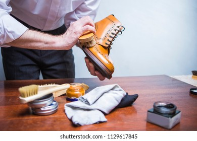 Professional Male Shoes Cleaner Using Brush For Polishing Male Tan Brogue Derby Boots. Variety of Cleaning Accessories Used.Horizontal Image Composition