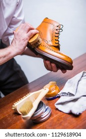 Professional Male Shoes Cleaner Using Brush For Polishing Male Tan Brogue Derby Boots. Variety of Cleaning Accessories Used. Vertical Image Composition