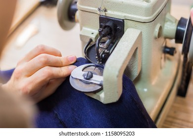Professional male skinner, furrier using special sewing machine for stitching fur skin at atelier, workshop. Fashion and leatherwork concept