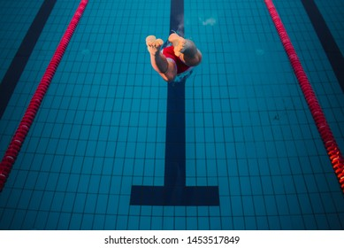 Professional male swimmer jumping into swimming pool.