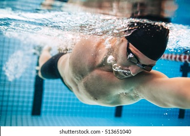 Professional male swimmer practising in swimming pool. Underwater shot of young sportsman swimming in pool.