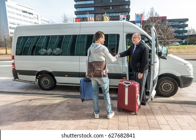 Professional male taxi driver shaking hands with man by van at airport