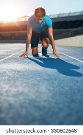 Professional male track athlete in set position on sprinting blocks of an athletics running track in stadium.