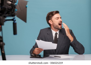 Professional male tv reporter is very tired. He is sitting at desk and yawing with closed eyes. The man is holding documents at studio. Isolated on blue background