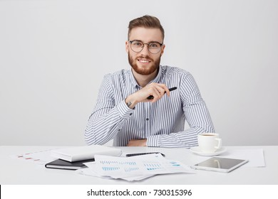 Professional male worker with thick beard and trendy hairstyle, wears round glasses and formal shirt, sits at work plae, drinks coffee, works with documents. Hipster young guy being busy working