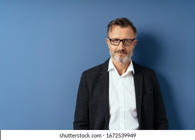 Professional man in a black blazer wearing glasses looking thoughtfully at the camera posing over a blue studio background with copy space