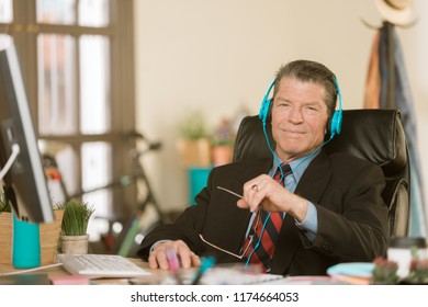 Professional man in a creative office listening to music or other media
