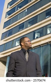 A professional man in front of an office building