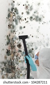 Professional man in protective clothing using a mechanical cleaner or steamer to clean mold growth off a wall of a house