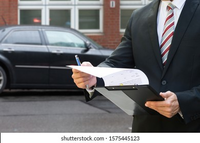 Professional Man Standing In Front Of Black Car Holding Clipboard In His Hand