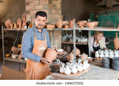 Professional man and woman potters at the work in pottery