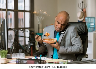 Professional man working through lunch eating packaged food