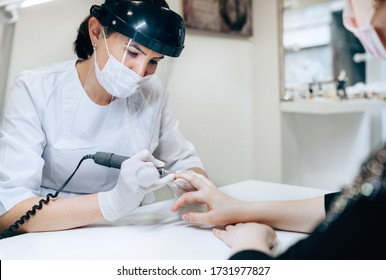 Professional manicure master in Transparent Safety Face Shield using Electric Nail Polisher Tool for Glazing treatment manicure procedure. Small business existence at COVID-19 lockdown concept.