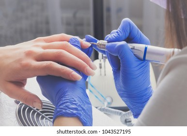 Professional manicure process in beauty salon. Closeup manicurist with a milling cutter for manicure. Procedure for cleansing cuticles on nails