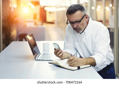 Professional marketing expert in stylish optical writing information in notepad making research via smartphone.Prosperous male entrepreneur noting contact of banking service standing in office