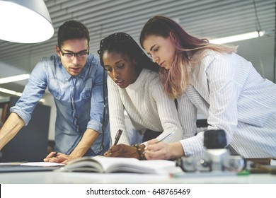 Professional marketing experts developing advertising campaign making planning together project working overtime in coworking space, talented young designers checking graphics and accounting