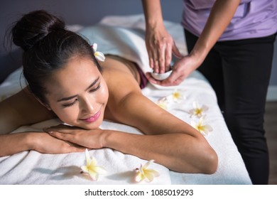 Professional massage therapist applying oil and cream in hand and  ready to start in Thai spa salon while happy beautiful tan Asian female with plumeria flower relax on bed.