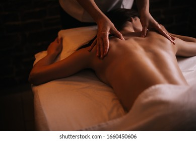 Professional massage therapist massages the back of young unrecognizable woman lying on massage table, close-up. Beautiful naked girl with perfect skin gets relaxing massage. Concept of body care.