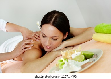 Professional massage therapist relaxing tensed muscles of her client