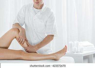 Professional masseur doing manual lymphatic drainage, light interior