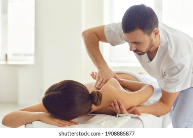 Professional masseur or manual therapist massaging young woman's shoulder, easing pain and relaxing muscles. Female patient getting remedial body massage in health clinic or physiotherapy center