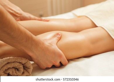 Professional masseur massaging female legs. Relaxing spa procedures, whole body massage, free space. Pleasure, rest, body care, beauty, alternative medicine, stress relief concept