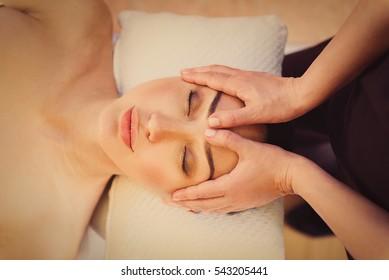 Professional masseuse massaging female face