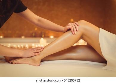 Professional masseuse massaging foot of girl