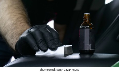 A professional master in automobile salons in black gloves imposes nano ceramics for leather using an applicator (sponge, fiber) that gives the salon a shine. Concept of: Car wash, Nano Service.