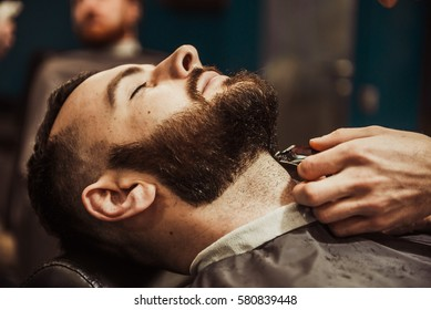 Professional Master hairdresser cuts client beard. Barber Men