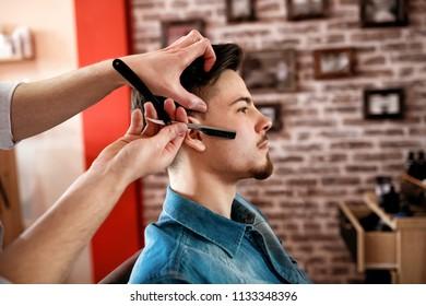 Professional master hairdresser shaves client beard in barbershop salon