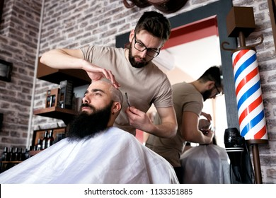 Professional master hairdresser shaves client head in barbershop salon