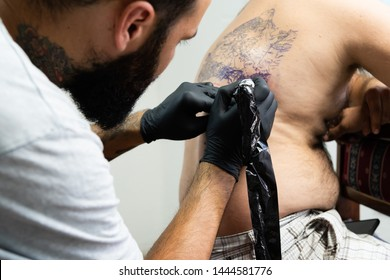 Professional master tattoo artist drawing tattoos picture on man's back using machine wearing black gloves at studio salon body art