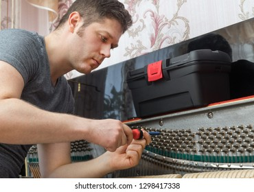 Professional master tuning the piano with ratchet tool.