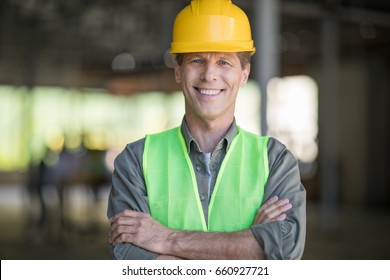 Professional mature architect in protective workwear standing with crossed arms and smiling at camera