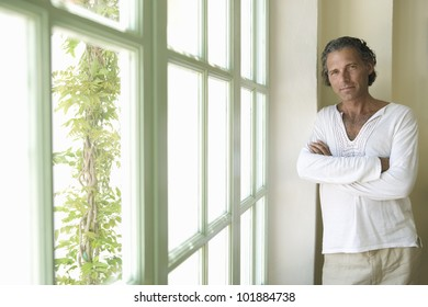 Professional mature man at home leaning by a large window and smiling at camera.