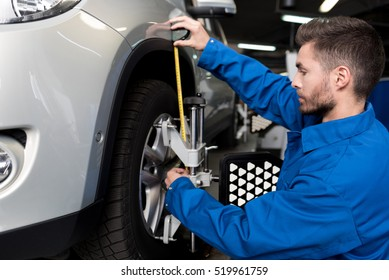 Professional mechanic adjusting automobile wheel alignment