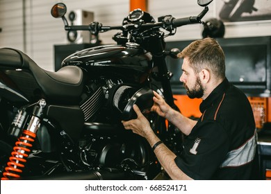 Professional mechanic change the air filter in the motorcycle. Handsome young man repairing motorcycle in repair shop.