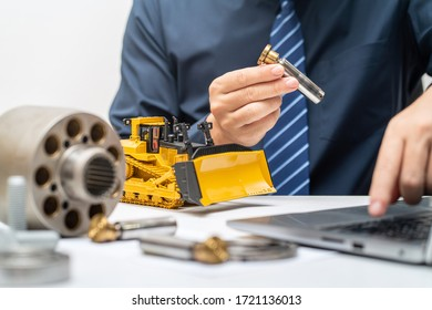 Professional mechanic engineer inspecting piston shoe of hydraulic piston pump and writing reports for during working day in office, repair maintenance heavy machinery concept