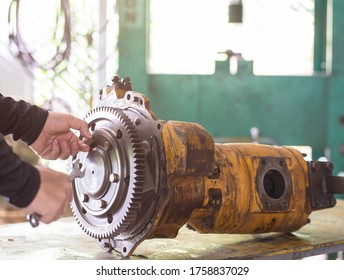 Professional mechanic engineer loosing bolt of gear hydraulic piston pump, repair maintenance heavy machinery concept