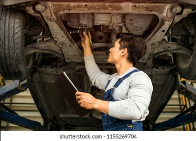 Professional mechanic with examining under the car at repair garage