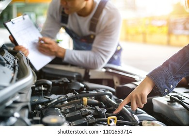 Professional mechanic holding a clipboard of service and check engine in garage. Repair service.